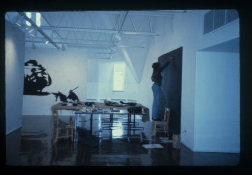 The artist stands on a chair, drawing on a large black piece of paper in white chalk, with an artwork in the same style installed on the wall behind.