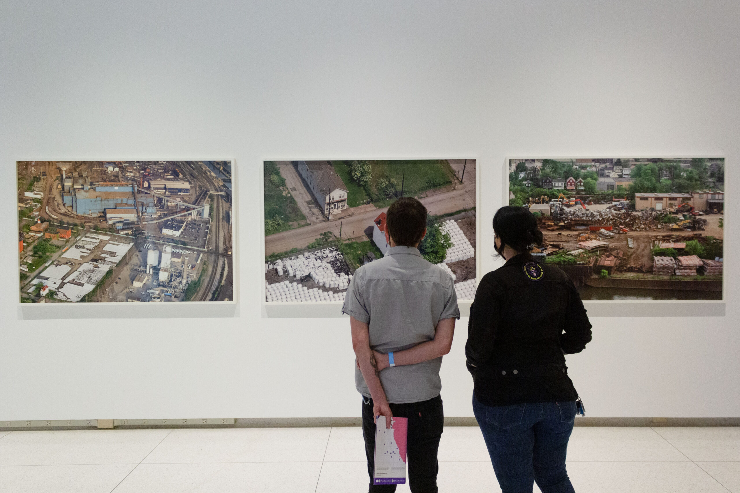 Two people looking at three large color photographs on a gallery wall