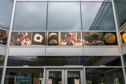A gold frieze depicting images from the Bud Billiken parade and images of an eclipse and the moon