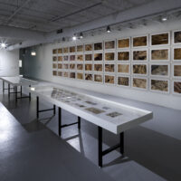 An installation with a grid of photographs depicting aerial vantages of the desert with white vitrine tables in the foreground
